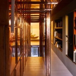 Interior view of corridor showing copper stairway and bookshelves