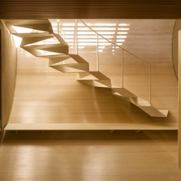 Interior view of steel stairway showing curved timber panelling