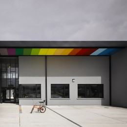Wide view of school entrance showing coloured soffit panels and bicycle