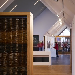 Interior view of exhibition space showing wattle and school group